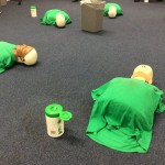 6 resuscitation dolls lined up on the floor ready for CPR training