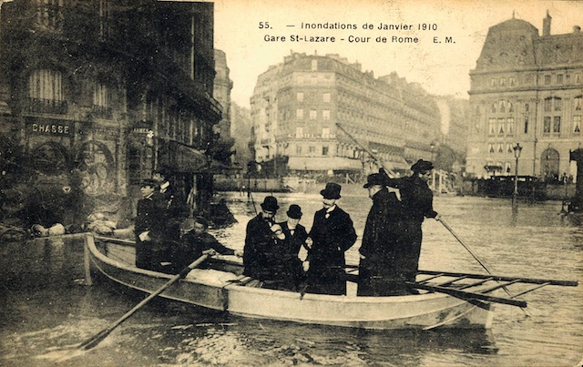 Sepia image showing half a dozen men in long coats and top hats being punted along a street in Paris.