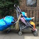 Photo of a buggy with a shopping caddy attached to the back carring two large bags of washing