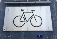 Metal panel with silhouette of bicycle frame cut into it mounted on a purple brick wall