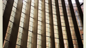 Verticle louvre windows at Coventry Cathedral. The windows are arranged on a curve. The window frames are deep, creating strong shadows and deep contrasts in the photo.