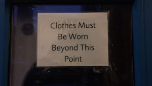 A sign that says 'Clothes Must Be Worn Beyond This Point'