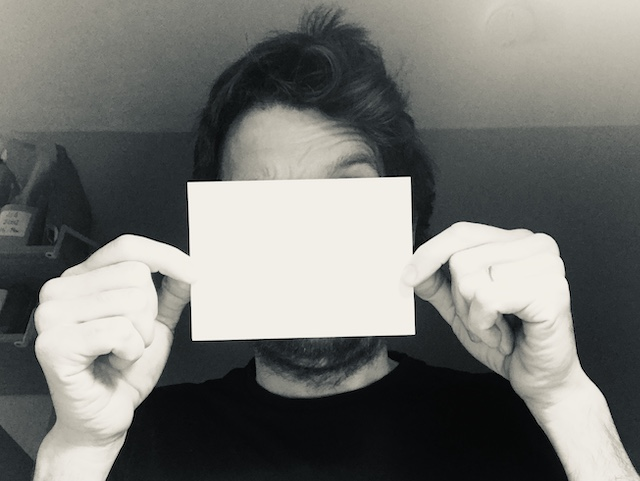 Oliver Broadbent holding up a blank sheet of paper to illustrate one of his answers to the question what is conceptual design