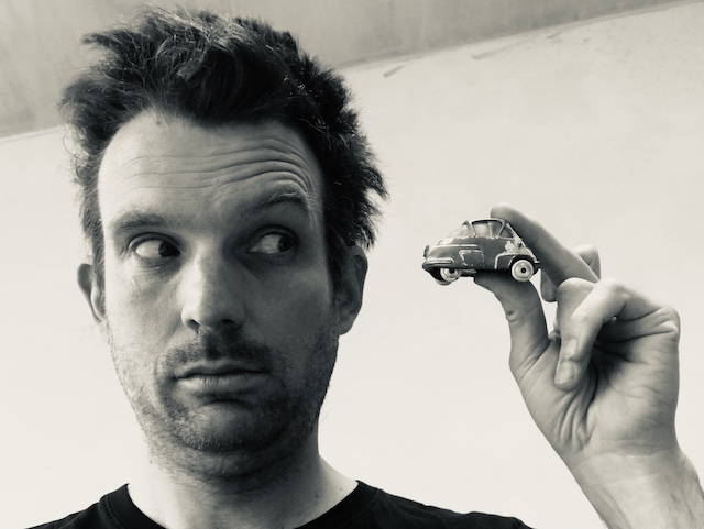 Oliver Broadbent holding a small model of a bubble car to illustrate a post asking will you always own a car