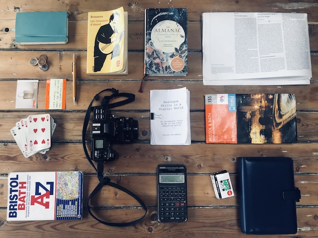 Image showing a range objects including a diary, a book of lyrics, a newspaper, cards, tickets, cash, maps, calculator and a camera, all things associated with Analogue Skills