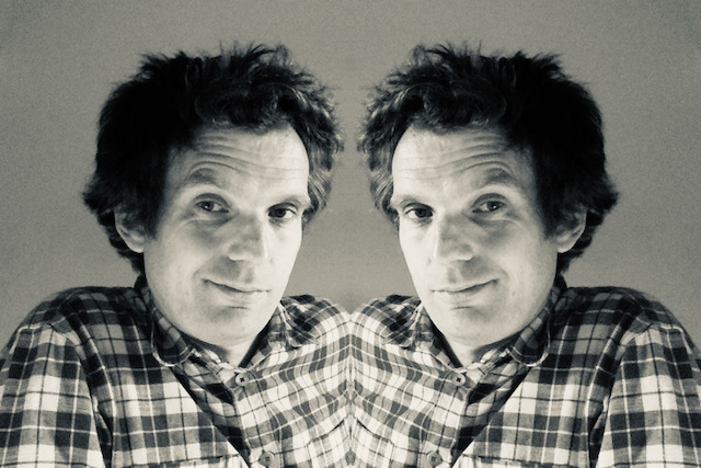 Image of Oliver Broadbent using a reflection filter to create a mirror image of himself - purpose is to illustrate a post about reflective workshops